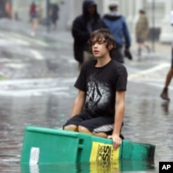 A boy floats on a newspaper box in a flooded street in the Soho section of Manhattan after Hurricane Irene passed over the New York City area August 28, 2011