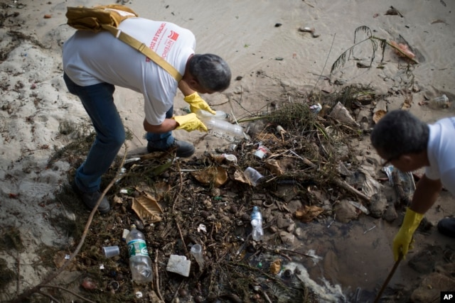 FILE - Health agents remove plastic bottles during an operation to eradicate the Aedes aegypti mosquito in Niteroi, Brazil, March 8, 2016.