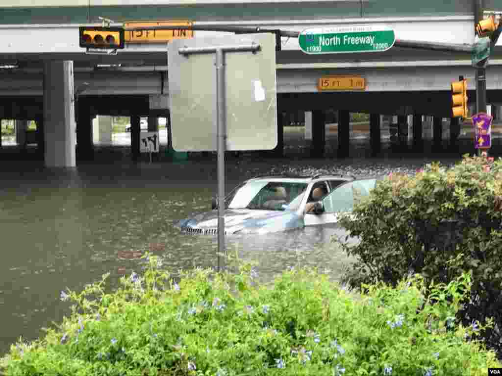 Floodwaters threaten to swallow a vehicle stranded on Interstate 45-North Freeway in Houston, Texas, Aug. 27, 2017. (C. Mendoza/VOA).