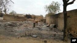 Cette photo prise avec un téléphone portable montre une jeune fille sur les ruines des maisons incendiées à Baga (21 avril 2013)