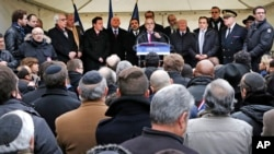 FILE - French Interior Minister Bernard Cazeneuve, center, speaks at a gathering against anti-Semitism also attended by Israel's ambassador to France, Yossi Gal, left, in Creteil, east of Paris, Dec. 7, 2014.