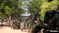South Sudan army soldiers hold their weapons as they ride on a truck in Bor, Dec. 25, 2013.