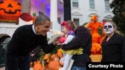 2014年10月31日奥巴马总统给一名到白宫过万圣节的儿童发食品(美国白宫)