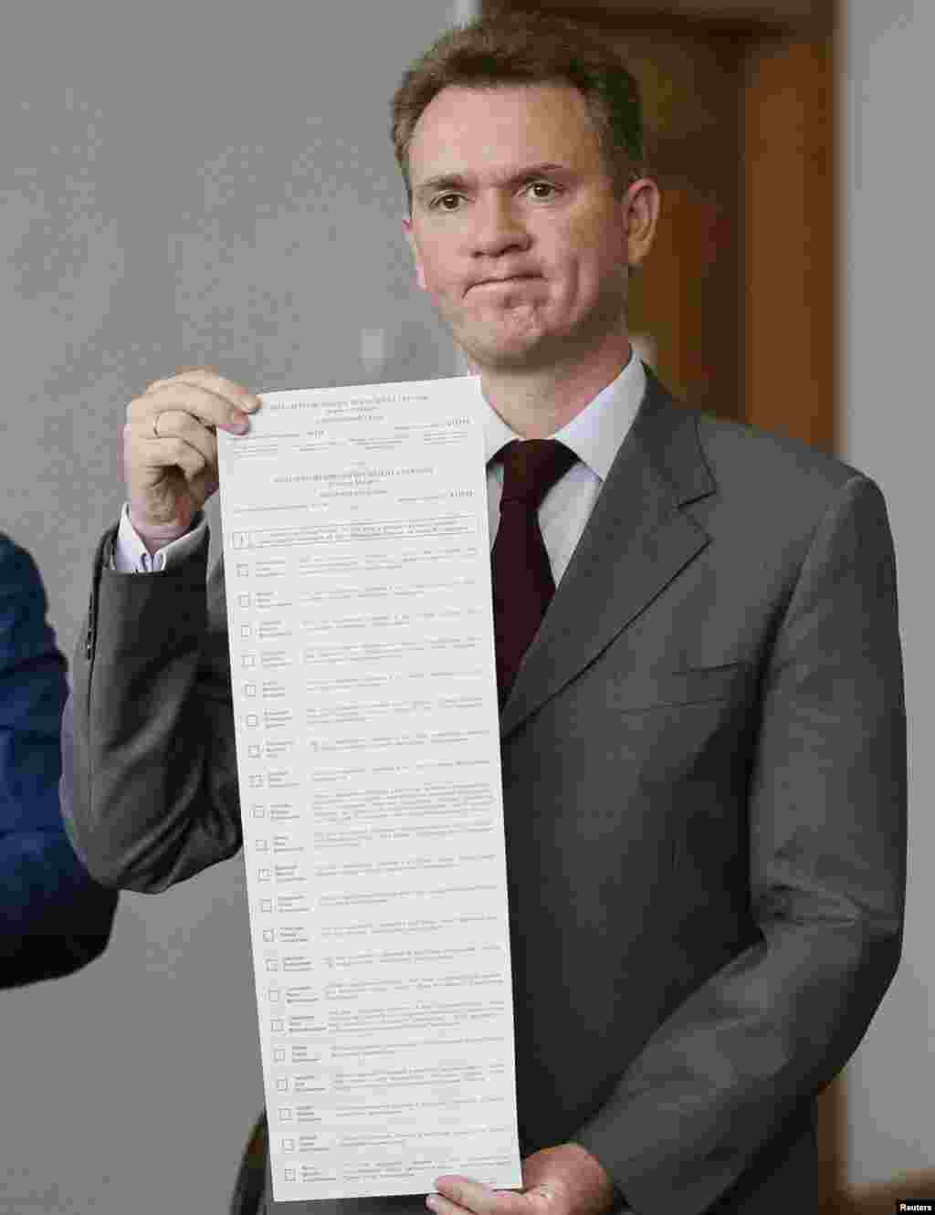 Mykhaylo Okhendovsky, head of Ukraine's Central Election Commission, shows a long ballot with names of 21 presidential candidates, at a news conference, in Kyiv, May 14, 2014.