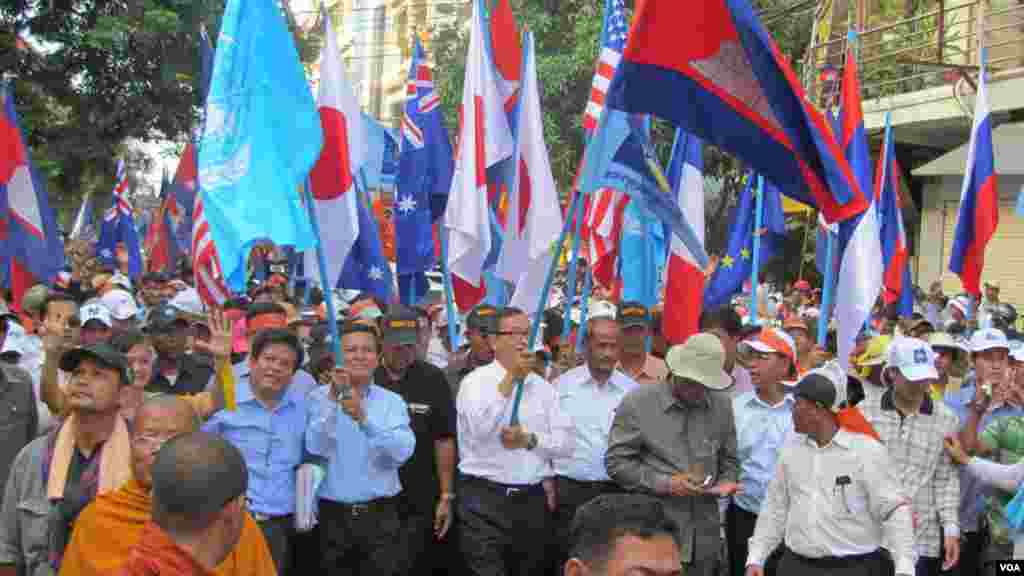 Opposition leaders Sam Rainsy and Kem Sokha hold U.N. and Cambodian flags along with their party flag while leading a march towards the U.N. office in Phnom Penh, Oct. 23, 2013. (Khoun Theara/VOA Khmer)