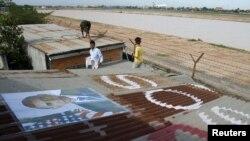 """Penduduk Kamboja di sekitar bandara Phnom Penh memasang foto Presiden Amerika Barack Obama di atap rumah mereka dan menuliskan """"SOS"""" sebagai permintaan dukungan agar tidak diusir dari rumah mereka (14/11). Sedikitnya delapan orang ditangkap karena aksi protes menjelang kunjungan Presiden Obama ke negara ini pekan depan."""
