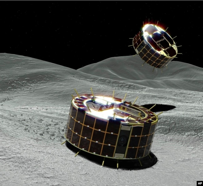 This computer graphic image provided by the Japan Aerospace Exploration Agency (JAXA) shows two drum-shaped and solar-powered Minerva-II-1 rovers on an asteroid. (JAXA via AP)