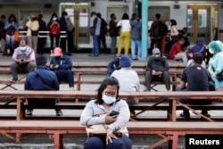 Warga memakai masker saat duduk di stasiun kereta pada jam sibuk, di tengah pandemi COVID-19 di Jakarta, 13 September 2021. (REUTERS/Ajeng Dinar Ulfiana)