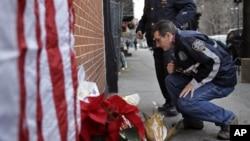 Un oficial de policía deja una vela cerca del sitio donde fueron asesinados dos policías en Brooklyn, Nueva York.