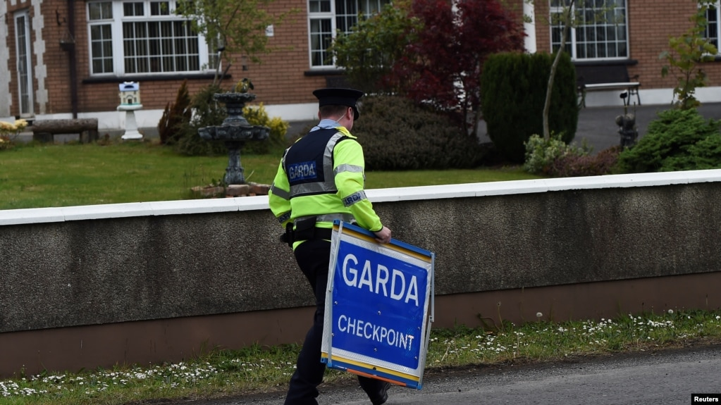 FILE - An Irish police officer removes a Garda checkpoint sign at the Armagh and County Louth border between Northern Ireland and Ireland, during a visit by European Union Chief Negotiator for Brexit Michel Barnier, May 12, 2017.