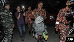 Petugas penyelamatan Malaysia (tengah) membawa bagian tubuh para korban dalam tas ransel di Kundasang, distrik Ranau, Sabau (6/6). (AFP/Mohd Rasfan)