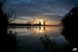 FILE - The coal-fired Plant Scherer, one of the nation's top carbon dioxide emitters, stands in the distance in Juliette, Ga., June, 3, 2017. U.S. President Donald Trump on June 1, 2017, pulled the U.S. from the Paris climate agreement, striking a major blow to worldwide efforts to combat global warming and distancing the country from its closest allies abroad.
