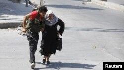 Seorang anggota Laskar Pembebasan Suriah membantu seorang perempuan menyeberang jalan di Aleppo (foto: dok). Seorang wartawan Jepang tewas saat menyertai pemberontak Suriah di Aleppo.
