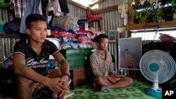 (រូបថតឯកសារ) អតីតទាសករនេសាទជនជាតិភូមាលោក Kaung Htet Wai (រូបឆ្វេង) និង លោក Lin Lin អង្គុយក្នុងបន្ទប់តូចមួយ ក្នុងខ្ទមក្នុងទីក្រុង Yangon ប្រទេសមីយ៉ាន់ម៉ា។