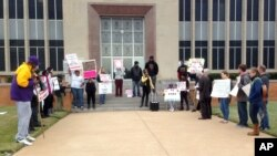 About two dozen people demonstrated outside the Waller County Courthouse in Hempstead, Texas, Jan. 6, 2016.