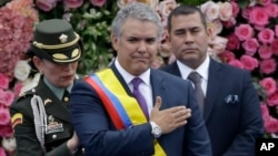 FILE - Colombia's President Ivan Duque gestures after receiving the presidential sash during his inauguration ceremony in Bogota, Colombia, Aug. 7, 2018.