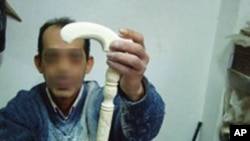 A carver displays an ivory walking stick, an item popular with Egyptian and Gulf Arab buyers