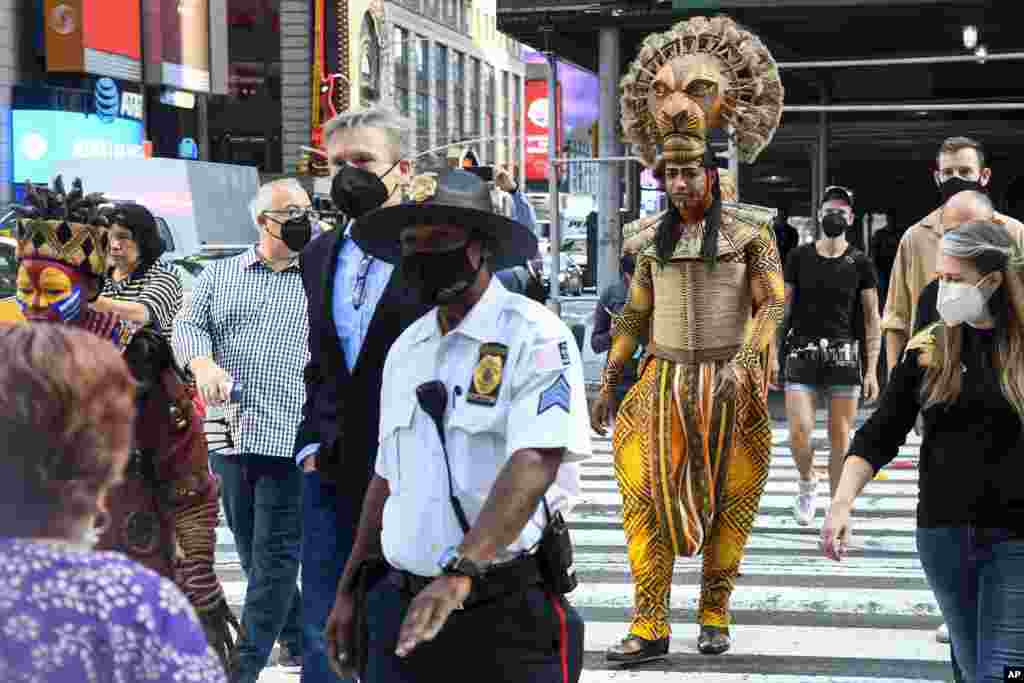 """Costumed cast members of Broadway's """"The Lion King,"""" L. Steven Taylor, as Mufasa, right, and and Tshidi Manye, as Rafiki, left, appear in Times Square to herald the return of Broadway theater in New York."""