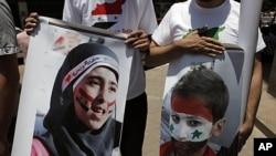 敘利亞反政府抗議者星期二手持受害者畫像進行示威