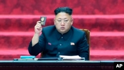 FILE - In this April 9, 2014, image made from video, North Korean leader Kim Jong Un holds up parliament membership certificate during the Supreme People's Assembly in Pyongyang, North Korea.