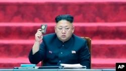 ຜູ້ນຳເກົາຫຼີເໜືອ ທ່ານ Kim Jong Un ຖືບັດສະມາຊິກສະພາ ຢູ່ທີ່ກອງປະຊຸມສະພາແຫ່ງຊາດ ປະເທດເກົາຫຼີເໜືອ.