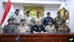 This photo released on his official Facebook page shows Iraqi Prime Minister Haider al-Abadi, center, surrounded by top military and police officers as he announces the start of the operation to liberate the northern city of Mosul from Islamic State militants, Oct. 17, 2016.