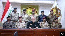 A photo shows Iraqi Prime Minister Haider al-Abadi, center, surrounded by top military and police officials as he announces the start of the operation to liberate Mosul, Oct. 17, 2016. Some say Baghdad intends to turn the city into a Shia stronghold.