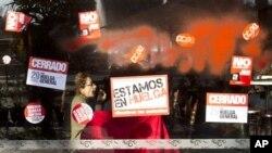 Seorang wanita duduk di belakang jendela bertuliskan 'Kami Mogok' dan 'Tutup untuk Mogok Kerja' di Madrid (29/3).