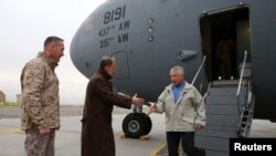 美国国防部长哈格尔(右)12月7日抵达喀布尔,受到美国驻阿富汗大使(中)的迎接