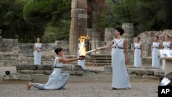 Actress Katerina Lehou, right, as high priestess, lights the torch during the lighting ceremony of the Olympic flame in Ancient Olympia, southwestern Greece, Oct. 24, 2017.
