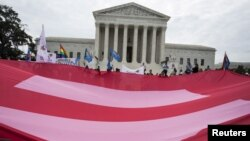 FILE - Supporters of gay marriage rally in front of the Supreme Court in Washington, June 26, 2015. A Massachusetts judge has ruled that an all-girls Catholic school violated state anti-discrimination law by rescinding a job offer to a gay man in a same-sex marriage.