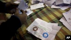 Petugas di TPS Mesir menghitung kertas suara dalam referendum terkait rancangan konstitusi baru yang kontroversial. (AP/Nasser Nasser)