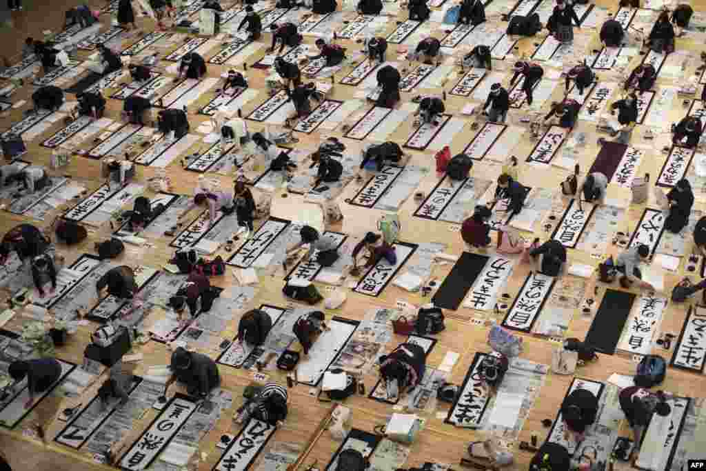 Participants write Japanese calligraphy during the annual New Year calligraphy contest in Tokyo.