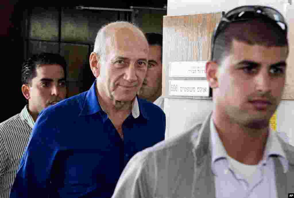 Former Israeli prime minister Ehud Olmert (center) leaves the Tel Aviv District Court in Israel, May 13, 2014.