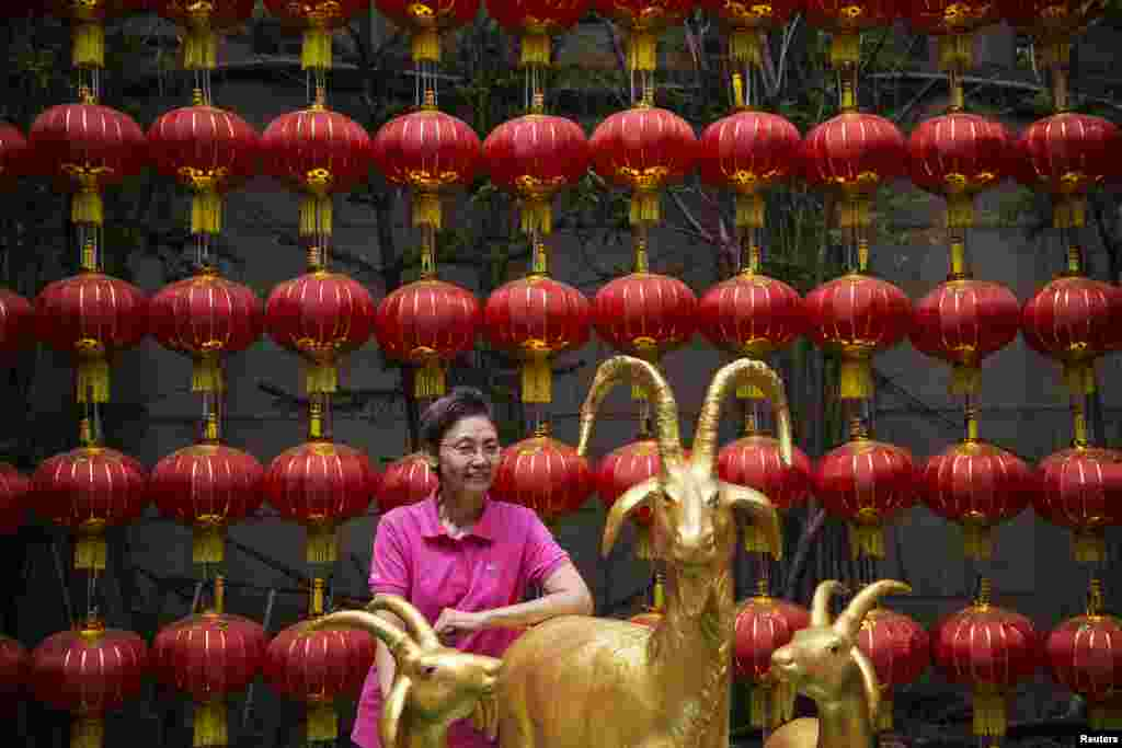A woman stands behind statues of goats at a temple decorated for the Chinese Lunar New Year in Chinatown, Bangkok, Thailand, Feb. 19, 2015.