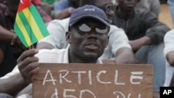 An opposition protestor holds a sign reading 'Faure, Resign,' referring to Togo's president, Faure Gnassingbe, and citing an article of the constitution that protesters say gives them the right to engage in civil disobedience, Aug. 25, 2012.