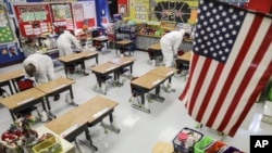 FILE - In this Nov. 5, 2020, file photo, custodial workers clean a classroom at Richard A. Simpson Elementary School in Arnold, Mo. The school went to fully virtual learning on Monday, Nov. 2, after more than 5% of the staff and students tested positive f