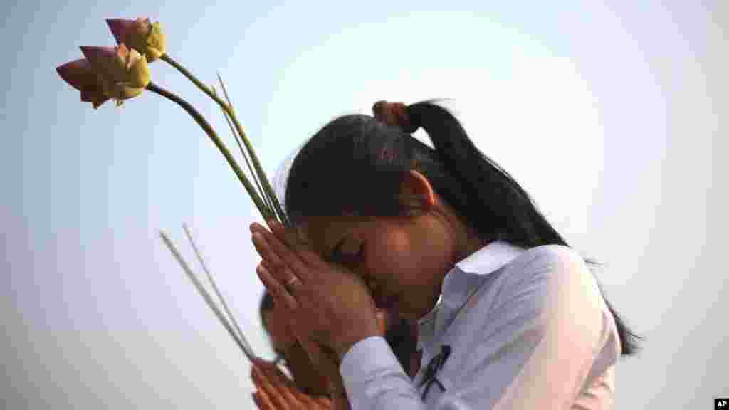 دو دختر در پنوم پن برای نوردوم سیهانوک، پادشاه پیشین کامبوج دعا می کنند.