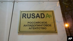 """Papan bertuliskan """"Badan Nasional Anti-Doping Rusia"""" di sebuah bangunan di Moskow. (AP/Alexander Zemlianichenko)"""