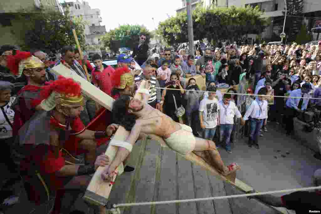 Lebanese Christians take part in a reenactment of the crucifixion of Jesus Christ on Good Friday beside Mar Joseph Chruch, Dhour Sarba, Lebanon, April 18, 2014.