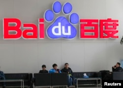 FILE - People sit in front of the company logo of Baidu at its headquarters in Beijing, China, Dec. 17, 2014.