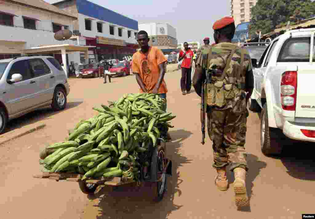 A Central African Republic soldier walks past a vendor on a street in Bangui, December 31, 2012.