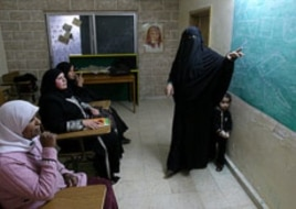 Rawiya Ali, right, a volunteer who teaches illiterate women, gives a class at a community service center marking International Women's Day, in Al Baqa'a Palestinian refugee camp, north of Amman, Jordan, March 8, 2011.