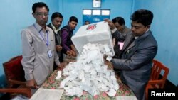 A polling officer pours ballot papers from a box onto a table to count during parliamentary elections in Dhaka, Bangladesh, Jan. 5, 2014.