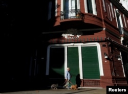 A woman walks her dogs in front of the facade of the Don Julio steakhouse, as the spread of the coronavirus disease (COVID-19) continues, in Buenos Aires, Argentina May 11, 2020. Picture taken May 11, 2020. REUTERS/Agustin Marcarian