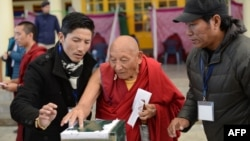 FILE - Palden Gyatso is guided as he casts his vote to elect a sikyong (prime minister) of the Central Tibetan Administration and lawmakers in McLeod Ganj, India, March 20, 2016. The Tibetan monk died Nov. 30, 2018, in Dharamsala, India, at age 85.