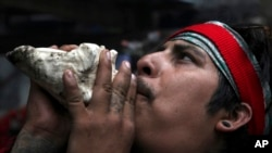 In this Friday, May 3, 2019 photo, a resident blows on a conch shell to honor Tonantzin, the Aztec mother earth goddess during the Day of the Cross celebrations on the flanks of the Iztaccíhuatl volcano or The Sleeping Woman. (AP Photo/Marco Ugarte)
