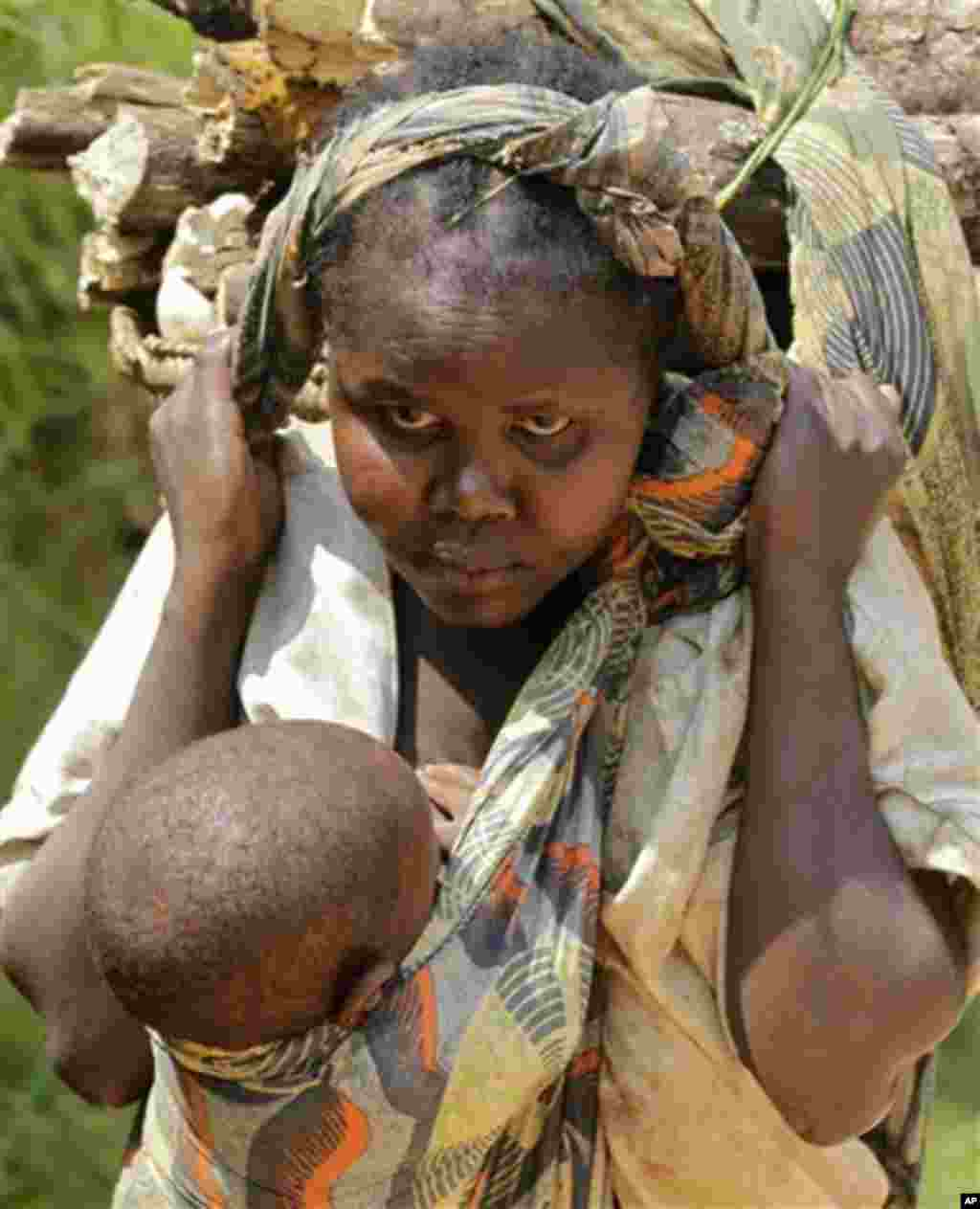 A woman carries a child and food stuff on a main road outside the small village of Walikale, Congo, Thursday, Sept. 16, 2010. According to aid workers, crimes like rape have been used as a brutal weapon of war in Congo, where conflicts based on tribal li