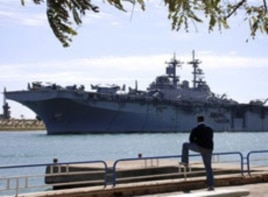 An Egyptian watches US amphibious assault ships USS Kearsarge as it sails at the Suez canal in Ismailia , Egypt, March 2, 2011