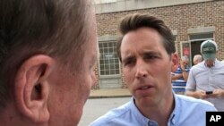 FILE - Republican U.S. Senate candidate Josh Hawley speaks with a man during a campaign rally in suburban St. Louis on Aug. 30, 2018.